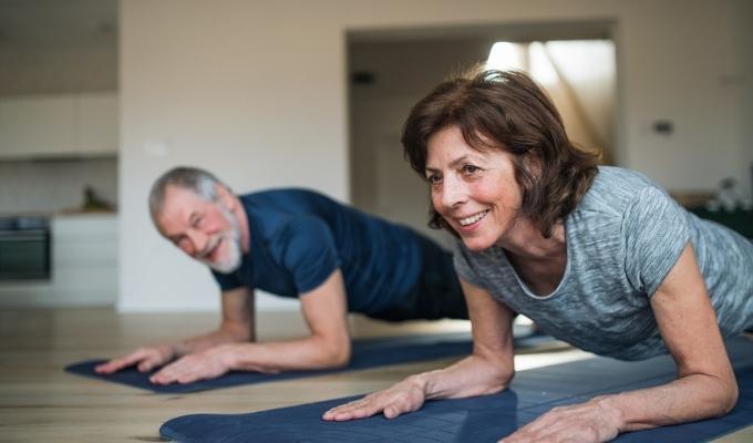 senior couple exercising at home, doing planks