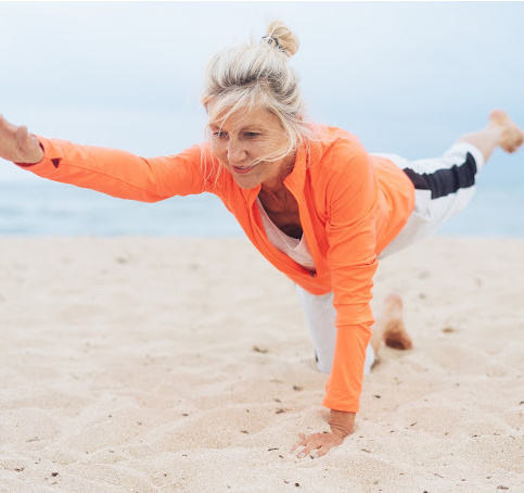 older woman doing a balance exercise on the beach