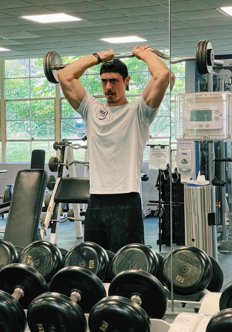 Jordan Pessolano, Personal Trainer, performing an overhead tricep extension.