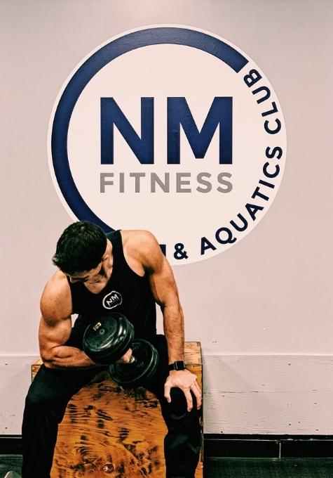 Jordan Pessolano, Personal Trainer, doing a concentration curl.